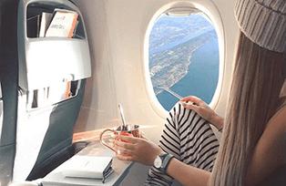 Студентка онлайн-школы ТОКИ летит в самолёте и смотрит в иллюминатор